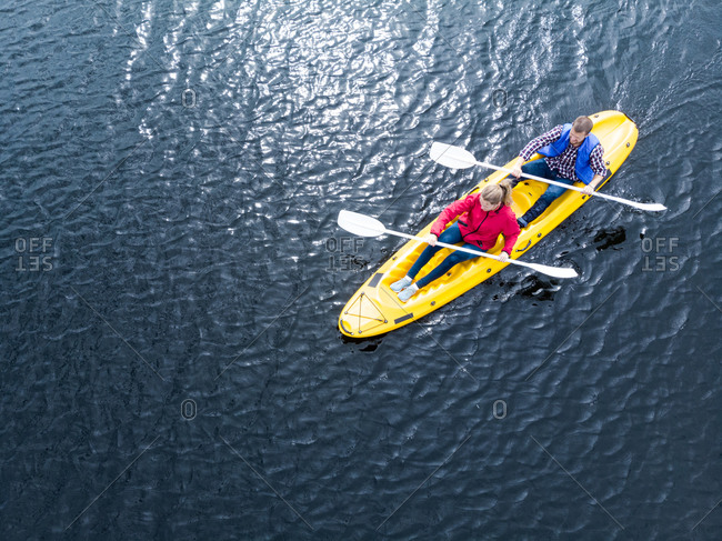 Drone shot of a Caucasian couple kayaking together in a yellow boat on calm water, both paddling with double-ended oars