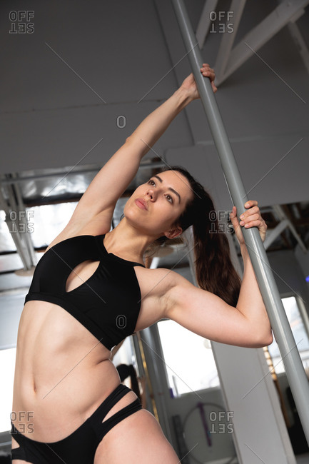 Front view of a fit attractive Caucasian woman enjoying pole dance training at a studio, holding the pole with both hands, looking up