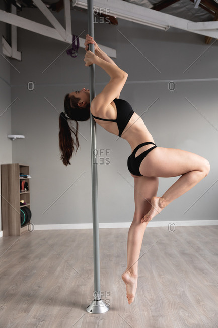 Side view of a fit attractive Caucasian woman enjoying pole dance training at a studio, holding the pole with both hands, lifting her body