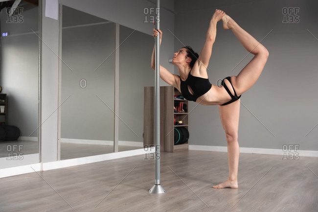 Side view of a fit attractive Caucasian woman enjoying pole dance training at a studio, holding the pole with one hand and her leg with the other hand, stretching