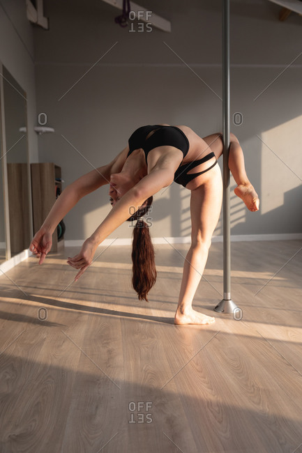 Front view of a fit attractive Caucasian woman enjoying pole dance training at a studio, holding the pole with her leg, stretching and bending backwards