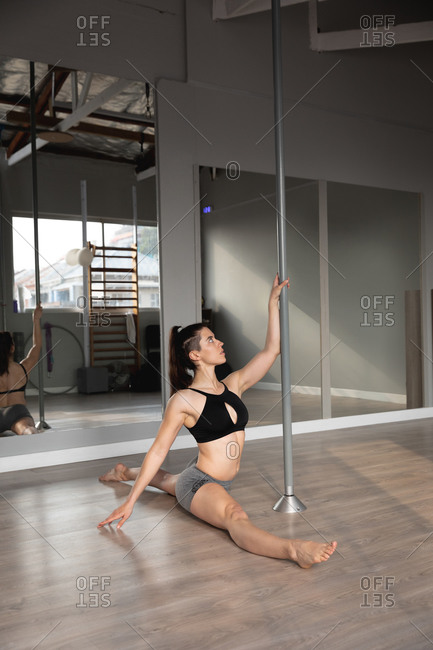Side view of a fit attractive Caucasian woman enjoying pole dance training at a studio, doing splits, holding the pole with one hand
