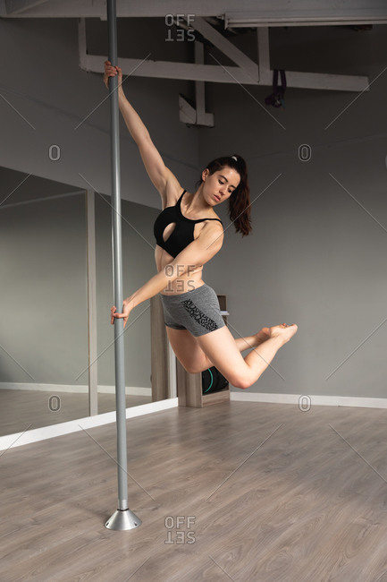 Front view of a fit attractive Caucasian woman enjoying pole dance training at a studio, holding the pole with both hands, lifting her body