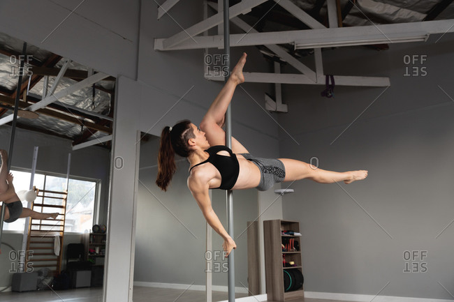 Side view of a fit attractive Caucasian woman enjoying pole dance training at a studio, lying vertically across the pole, holding it with one hand and with one leg raised