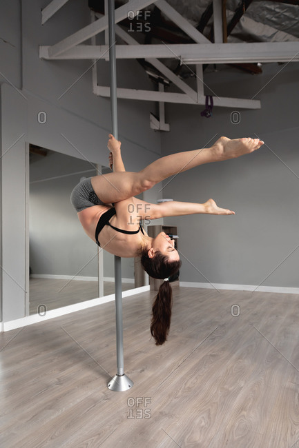 Side view of a fit attractive Caucasian woman enjoying pole dance training at a studio, hanging upside down on the pole with legs outstretched