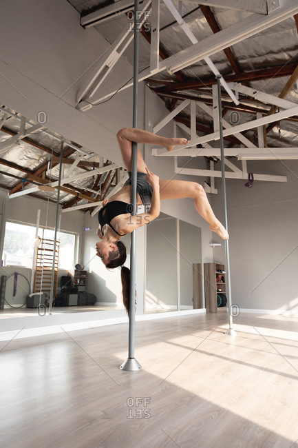 Side view of a fit attractive Caucasian woman enjoying pole dance training at a studio, hanging upside down on the pole, holding it with one leg