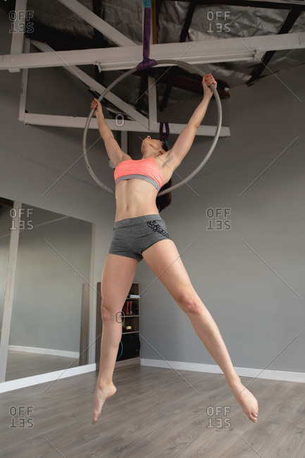 Front view of a fit attractive Caucasian woman enjoying pole dance training at a studio, hanging on a hoop, holding it with both hands