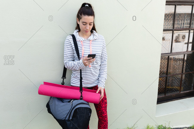 Front view of a fit Caucasian woman on her way to fitness training, carrying a sports bag and a yoga mat, standing on a street against a wall, using her smartphone