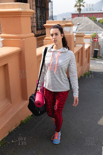 Front view of a fit Caucasian woman on her way to fitness training training on a cloudy day, carrying sports bag and a yoga mat