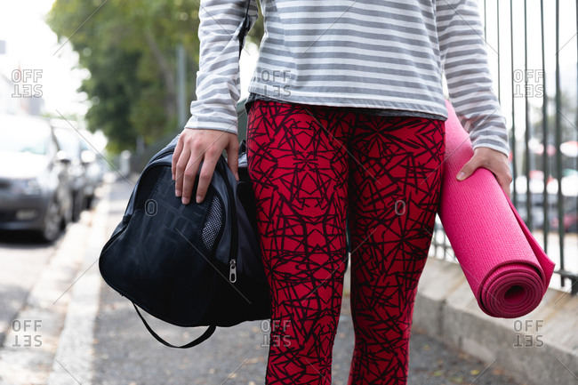 Front view mid section of a fit Caucasian woman on her way to fitness training on a cloudy day, carrying sports bag and a yoga mat
