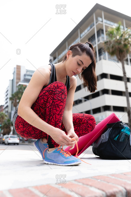 Front view of a fit Caucasian woman on her way to fitness training on a cloudy day, carrying a sports bag and a yoga mat, kneeling down in the street and tying her shoelaces