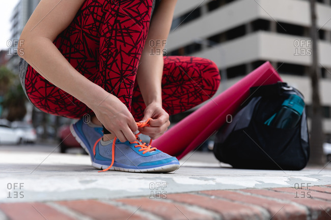 Front view low section of a fit Caucasian woman on her way to fitness training on a cloudy day, with a sports bag and a yoga mat, kneeling down in the street and tying her shoelaces