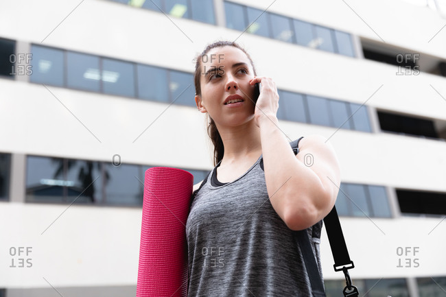 Front view of a fit Caucasian woman on her way to fitness training on a cloudy day, carrying a sports bag and a yoga mat, talking on a smartphone and walking in the street