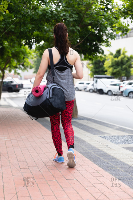 Rear view of a fit Caucasian woman on her way to fitness training on a cloudy day, carrying a sports bag and a yoga mat