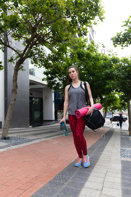 Front view of a fit Caucasian woman on her way to fitness training on a cloudy day, walking in the street carrying a sports bag and a yoga mat, holding a bottle of water