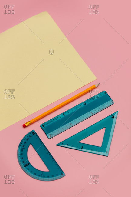 Paper and pencil with school supplies on pink background