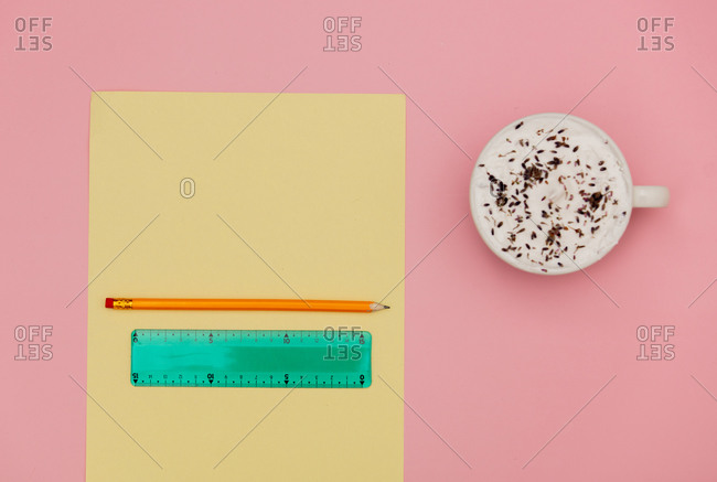 Cappuccino with lavender, paper with pencil and ruler on pink background