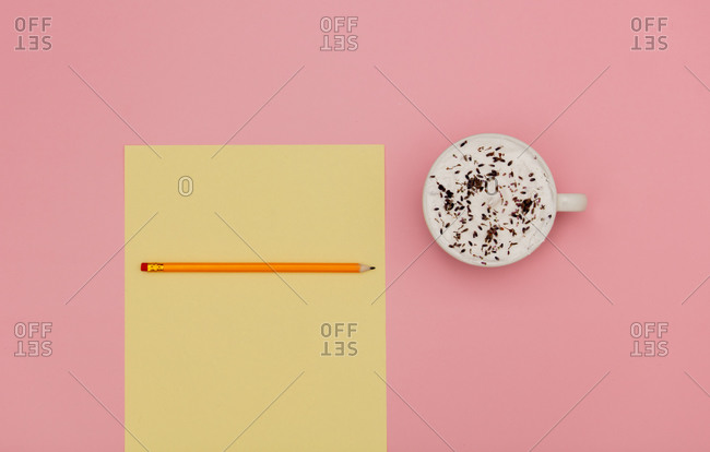 Cappuccino with lavender and paper with pencil on pink background