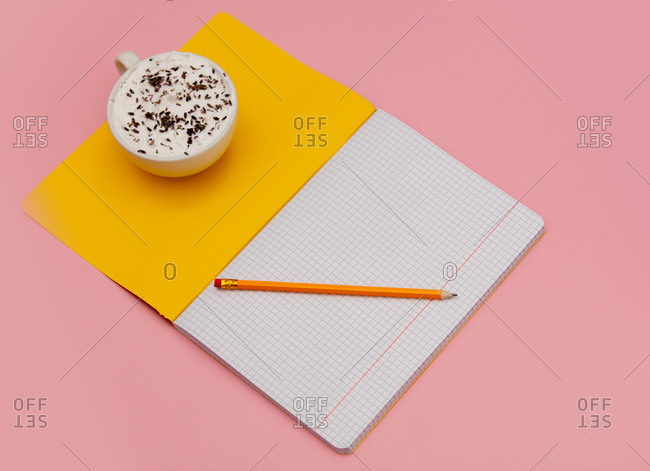 Cappuccino with lavender and notebook with pencil on pink background