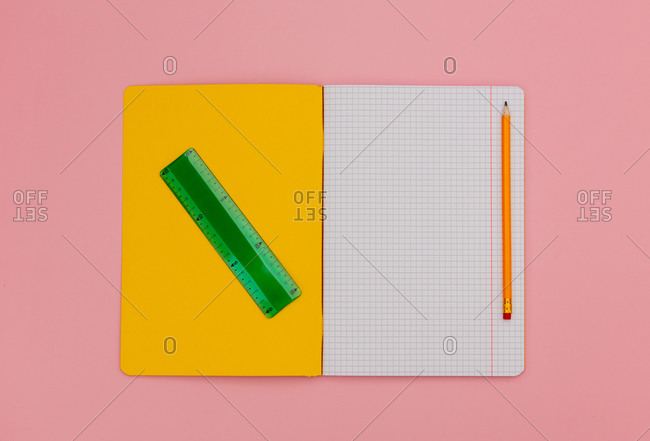 Yellow notebook with pencil and ruler on pink background