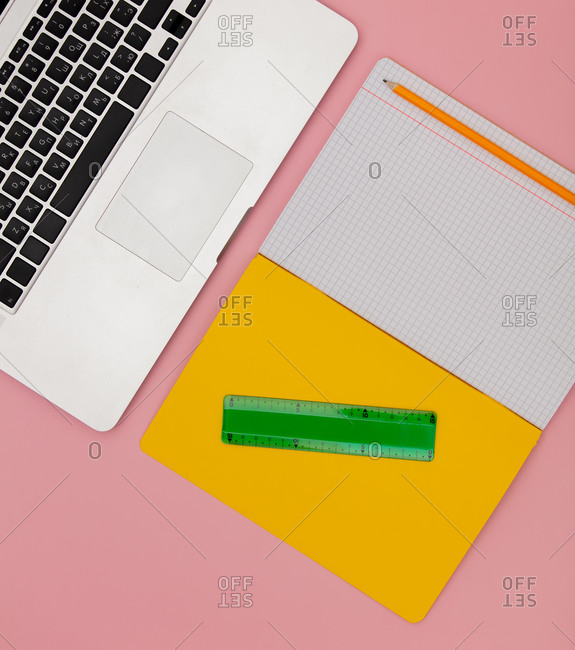 Laptop computer, supplies and notebook with pencil on pink background