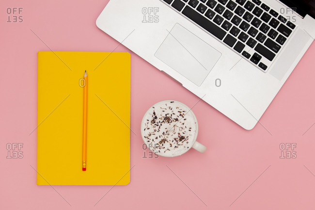 Cappuccino cup with notebook and pencil near laptop computer