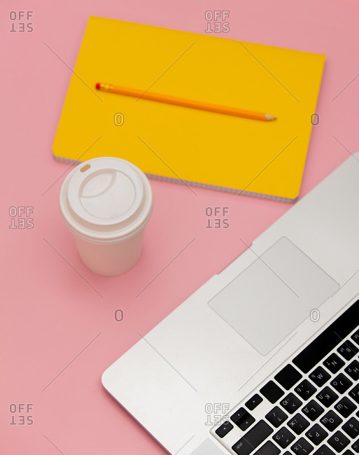 Takeaway cappuccino with notebook and pencil near laptop computer on pink background