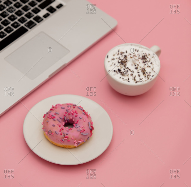 Cappuccino cup with notebook and donut on pink background