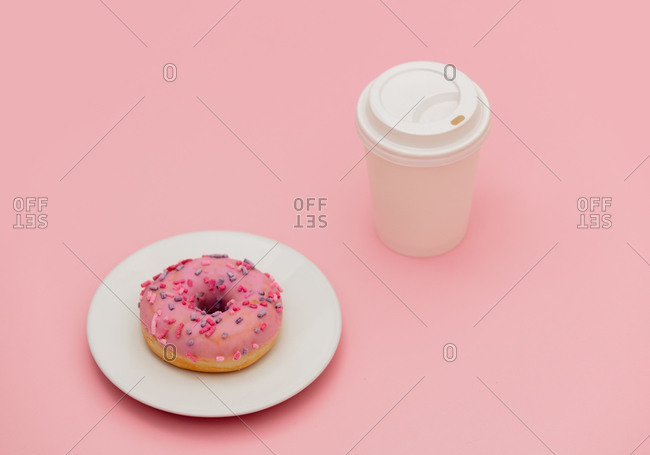 Takeaway coffee cup and donut on pink background