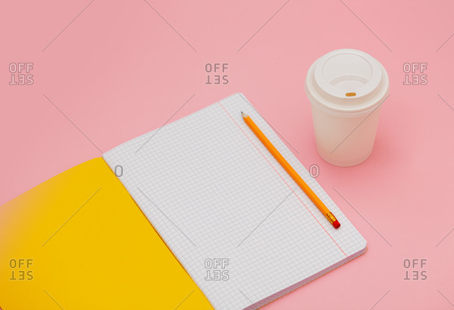 Takeaway coffee cup and notebook with pencil on pink background