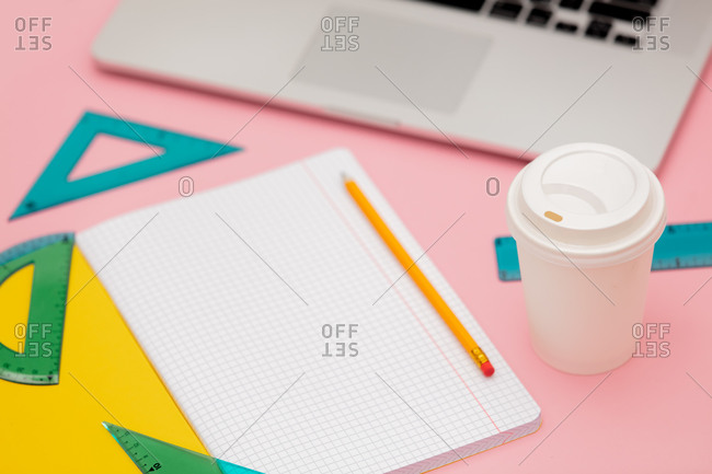 Takeaway coffee cup with notebook and laptop on pink background