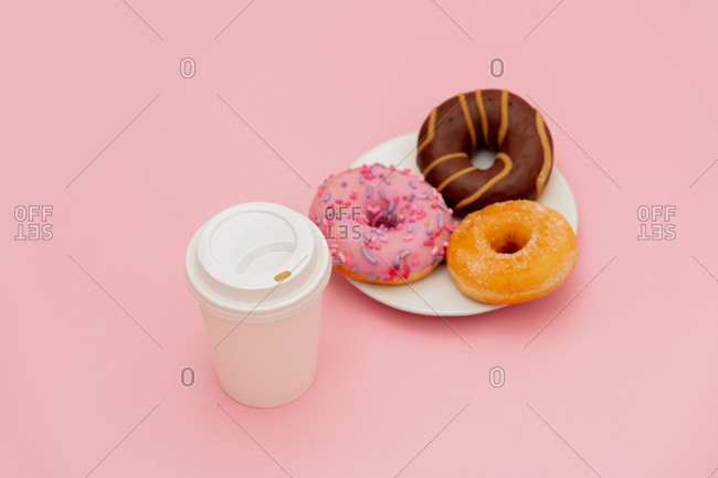 Donuts and takeaway coffee on pink background
