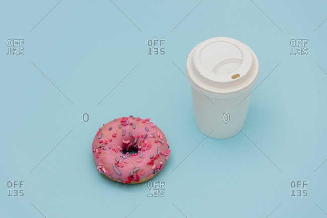Takeaway coffee cup and donut on blue background