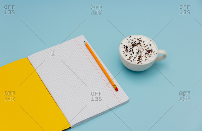 Cappuccino and notebook on blue background