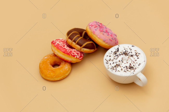 Donuts and takeaway coffee on yellow background
