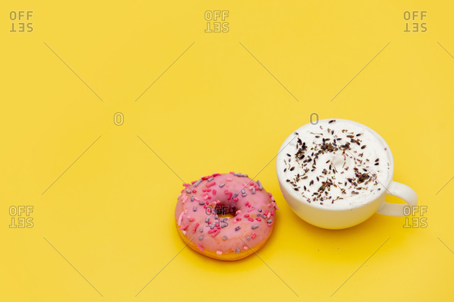 Donut and takeaway coffee on yellow background