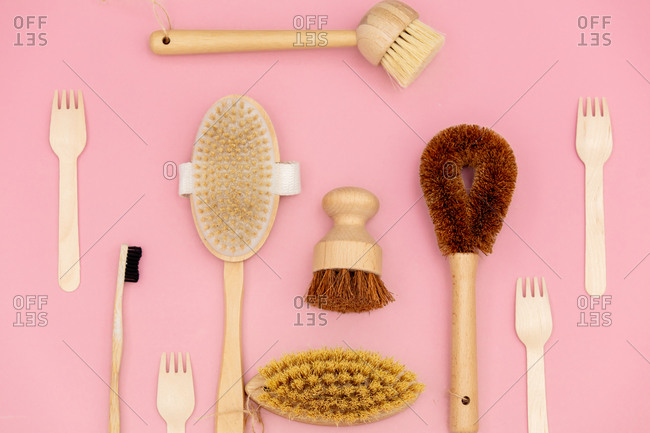 Eco-friendly wooden brushes on pink background. above view