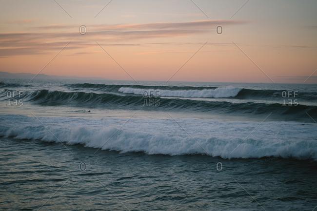 Big waves on Zurriola Beach in San Sebastian during sunset
