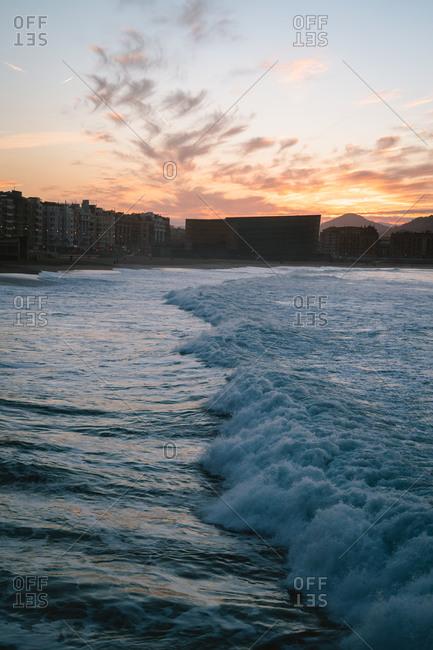 Big waves rolling into Zurriola Beach in San Sebastian during sunset