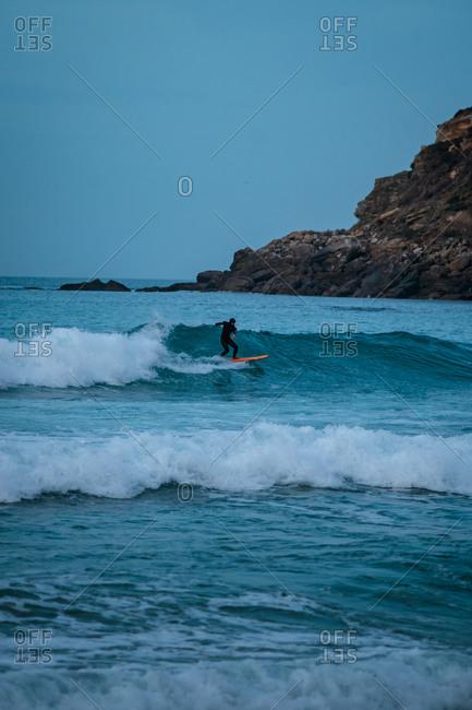 Surfer riding a wave on Zurriola Beach in San Sebastian