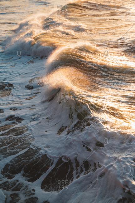 Big waves crashing on Zurriola Beach during golden hour