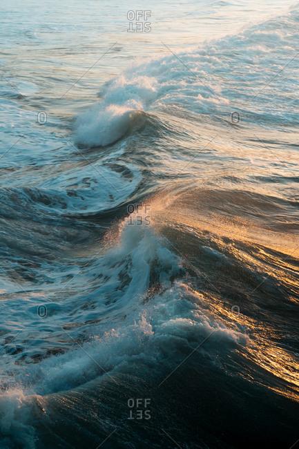 Big waves splashing on Zurriola Beach during golden hour