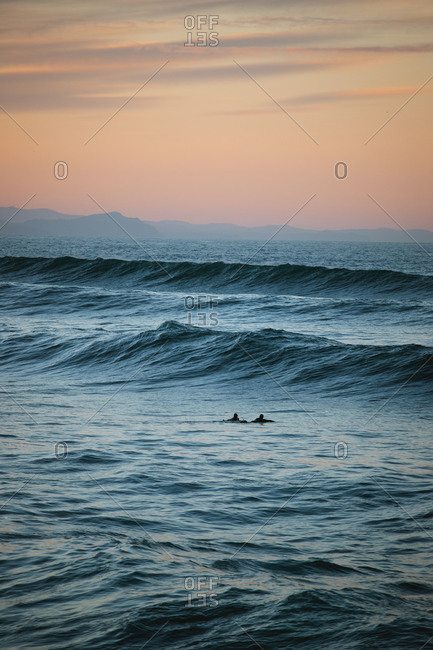 Two surfers paddling towards the waves at dusk