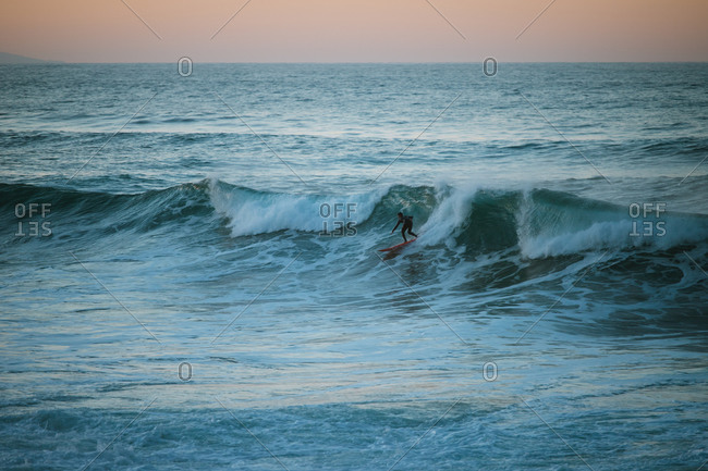 Surfer riding a wave during sunset