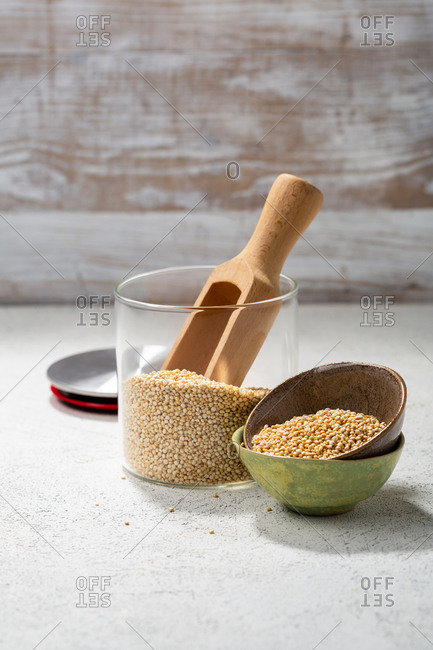 Quinoa in storage jar and small bowls with a wooden scoop