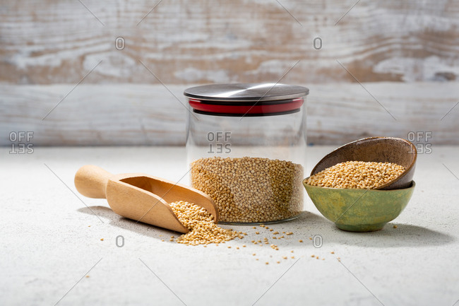 Quinoa in a glass jar beside small bowls with a wooden scoop