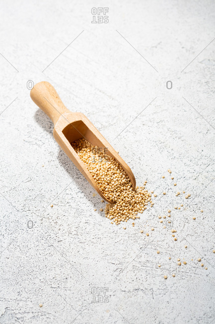Quinoa in a wooden spoon on white surface