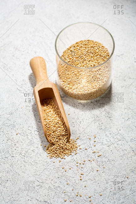 Quinoa in jar and wooden spoon on white surface