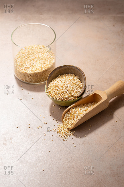 Quinoa in jar, bowl and wooden spoon