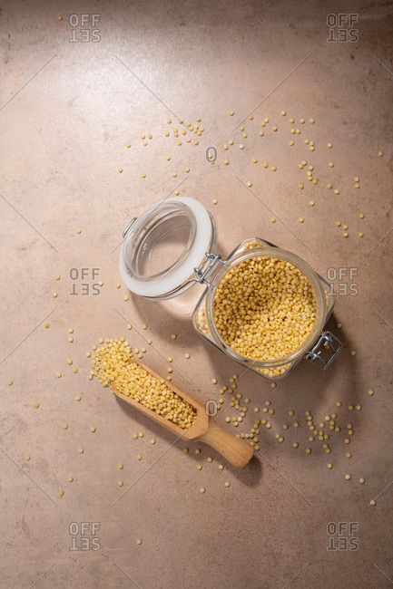 Overhead view of pasta ptitim on light surface with wooden scoop